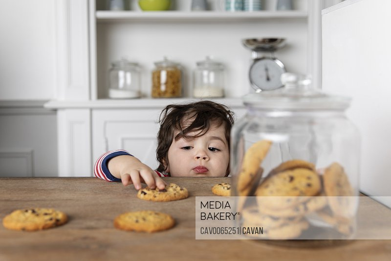 Young boy reaching for cookies on kitchen table
