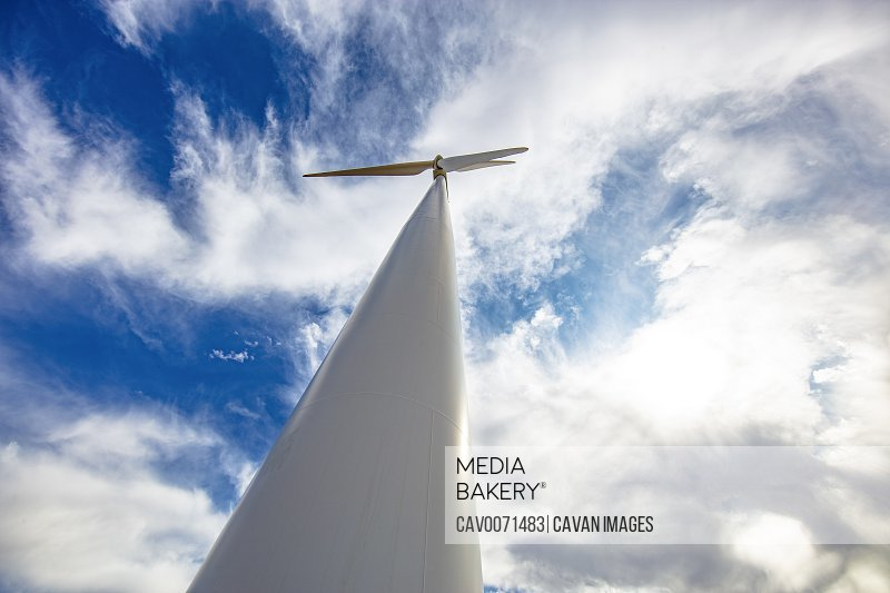 Wind Turbine low angle against cloudy blue sky