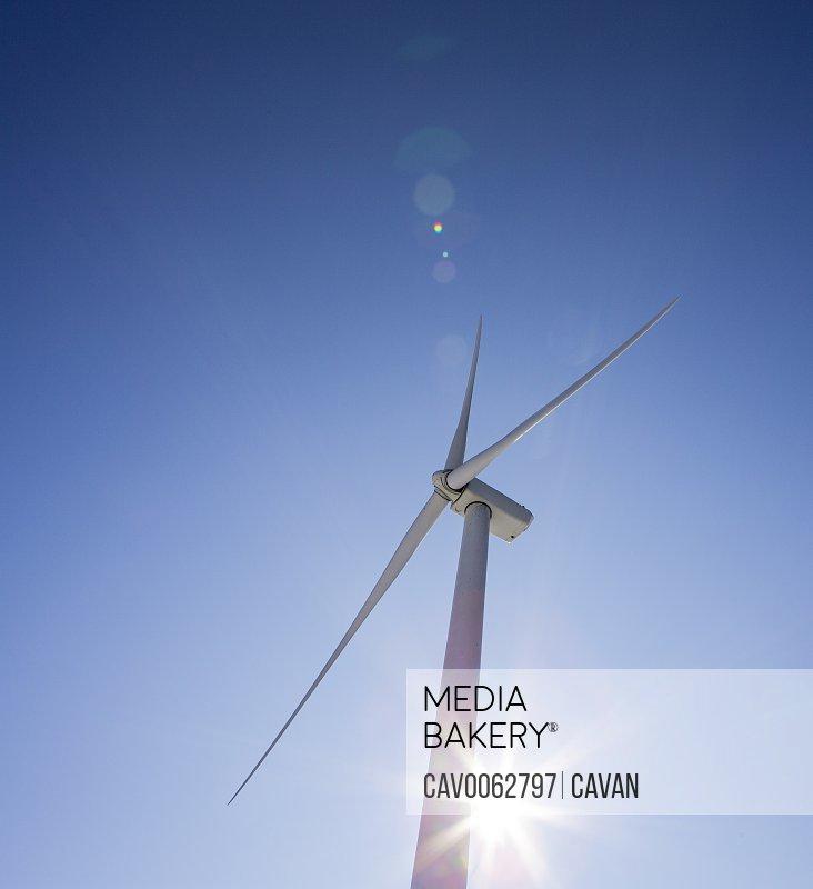 Wind turbines against blue sky with sun flare