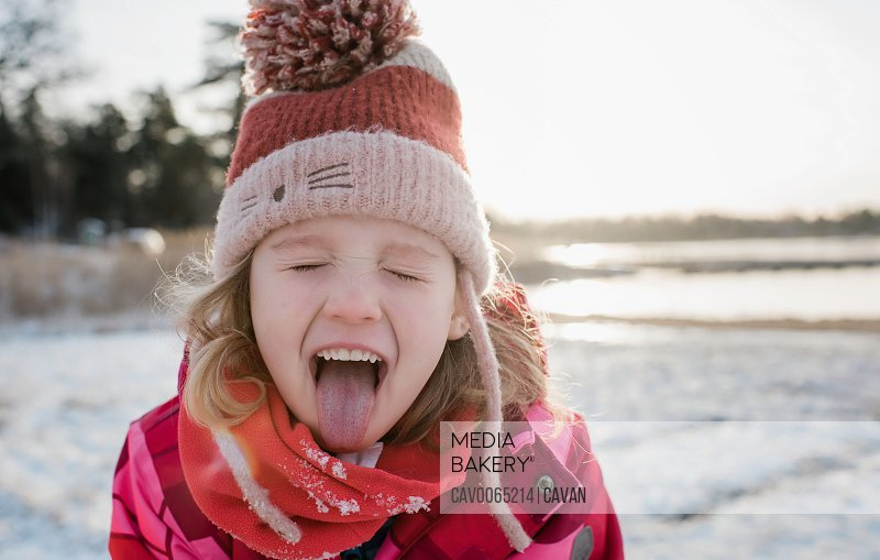 young girl catching snow with her tongue out whilst playing outside