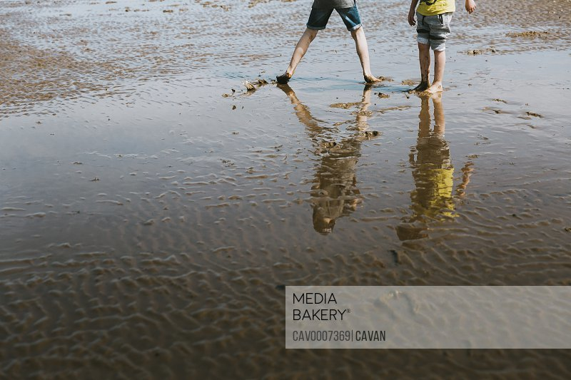 Reflection of two brothers playing on beach