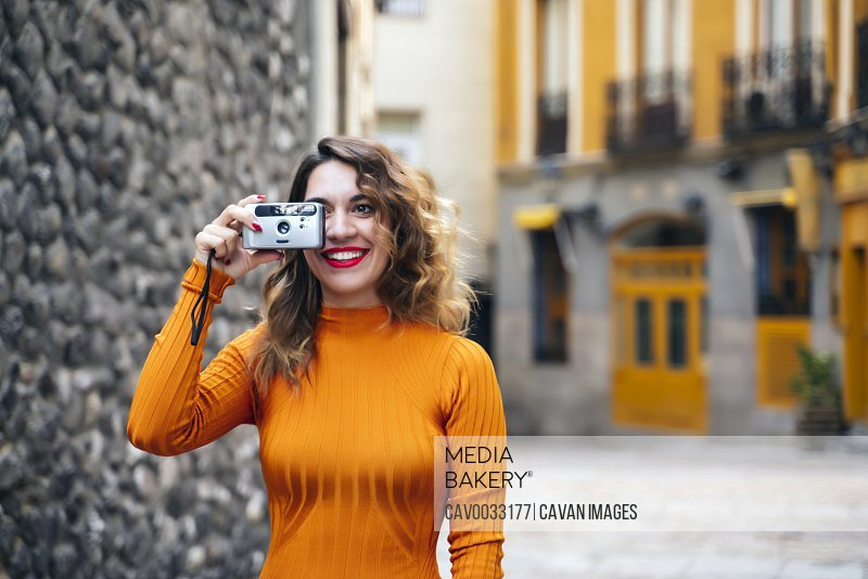 attractive young woman making photos in the street