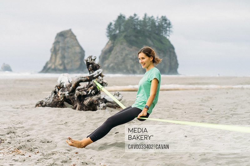 Girl is sitting on slackline at LaPush beach in Olympic National Park