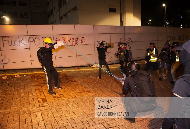 Protesters throwing stones with a slingshot at the Tsim Sha Tsui polic <br><br><span style='color: red'>Editorial Use Only.</span><br><br>