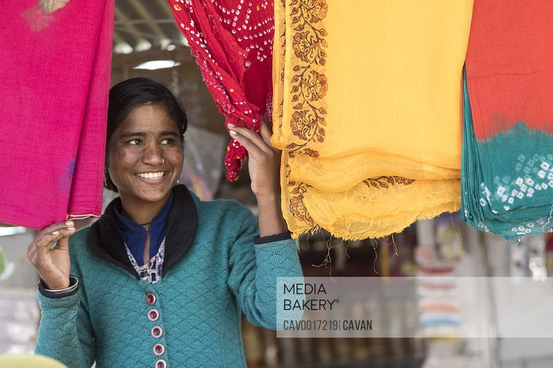 A young woman peek out between colorful Indian clothes and smiles. <br><br><span style='color: red'>Editorial Use Only.</span><br><br>