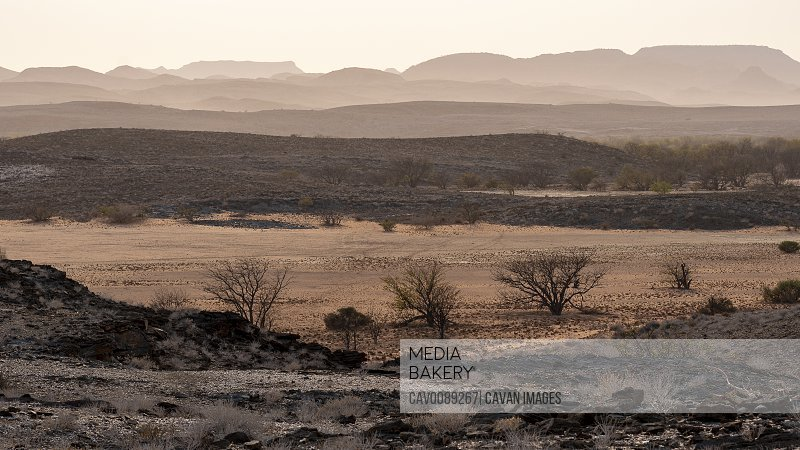 hilly and arid landscape of the Namibian desert at sunrise