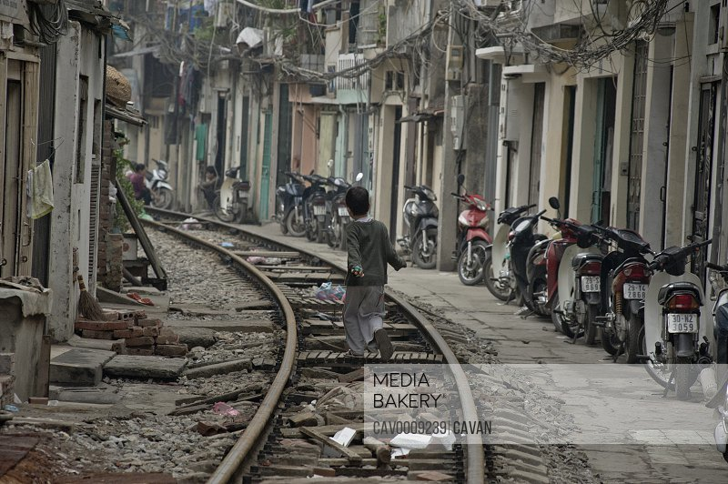 Boy runs on the railway line through the central slums of Hanoi <br><br><span style='color: red'>Editorial Use Only.</span><br><br>