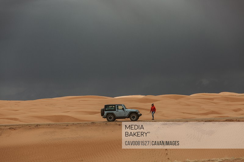 woman walks back to jeep under stormy skies in utah sand dunes