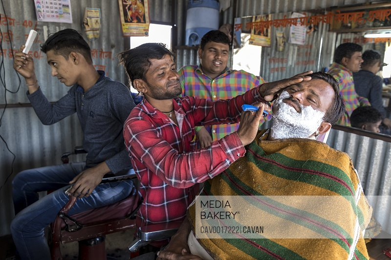 A man shaves another man in an Indian barber shop. <br><br><span style='color: red'>Editorial Use Only.</span><br><br>