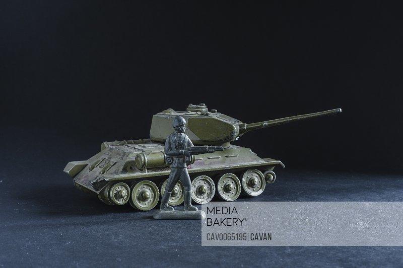 metal toy tank near a soldier