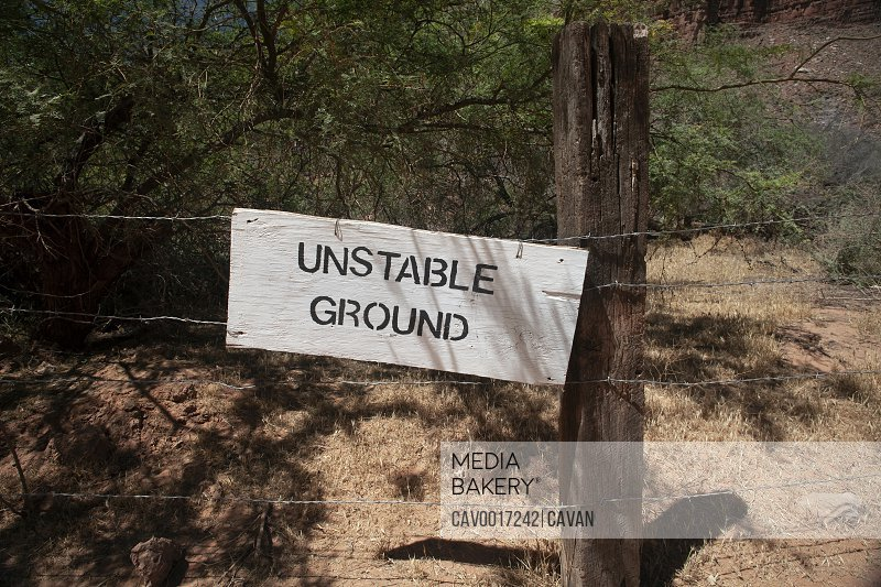 Wooden sign warning of unstable ground attached to barbed wire fence