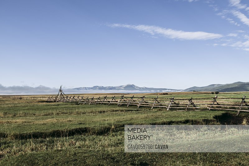 Morning mist a fence and distant mountains in the plains of Montana