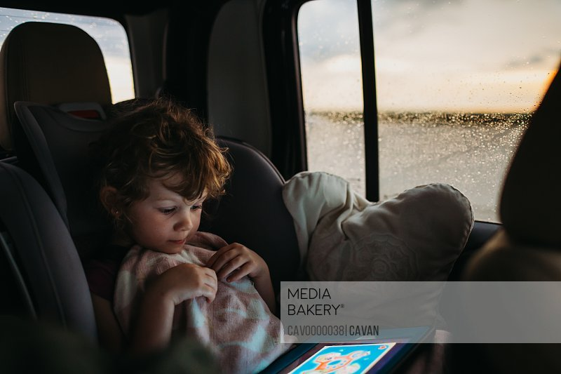 Young girl playing educational game on car ride home while it rains