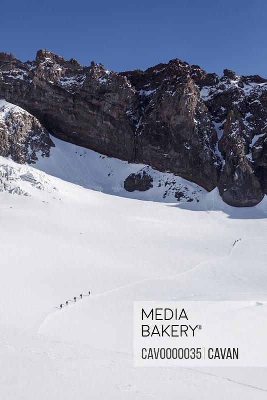 Climbing Rope Teams Descend a Trail Toward Camp Muir On Mount Rainier