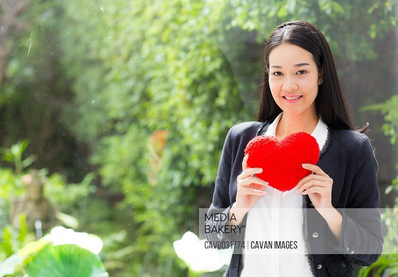 Red heart in businesswoman hand - Asian woman with hope concept.