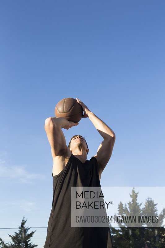 Young muscular man with basketball