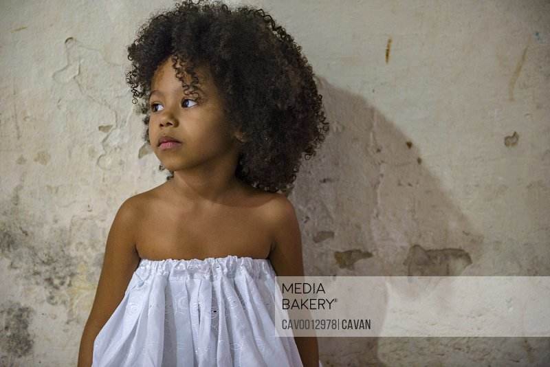 Beautiful Afro-Brazilian little girl with curly hair and white dress <br><br><span style='color: red'>Editorial Use Only.</span><br><br>