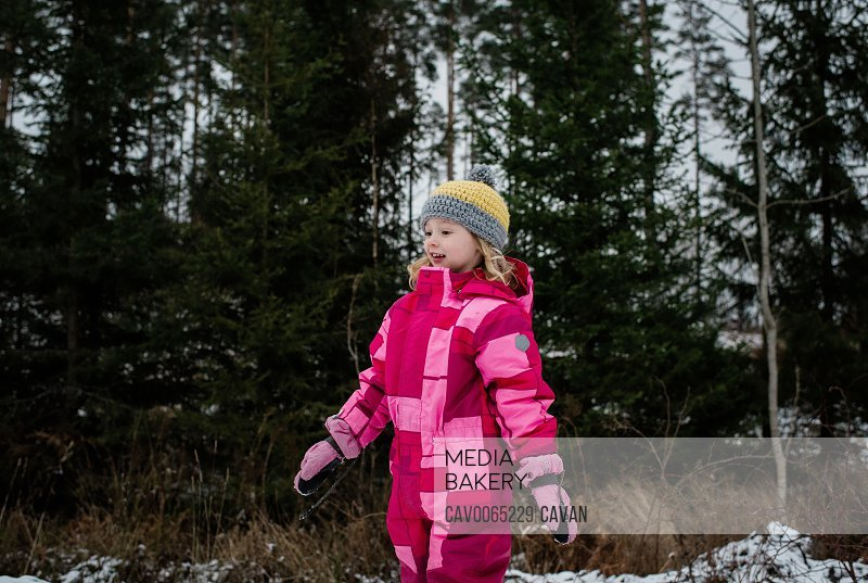 young girl walking in the snow in a snowsuit in winter