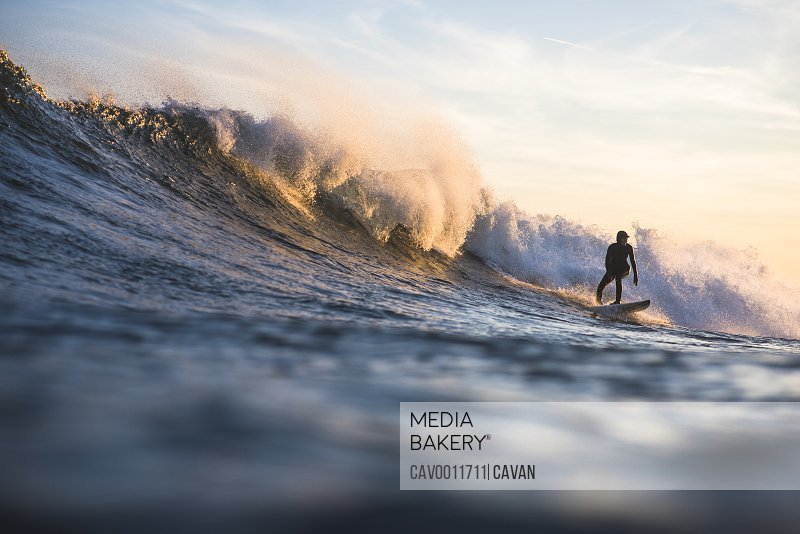 Woman enjoying golden hour winter surf