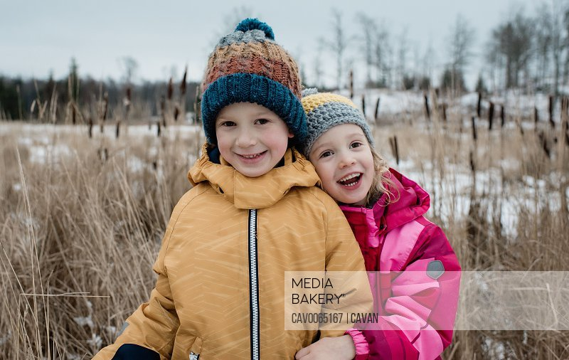 siblings cuddling and laughing whilst playing outside in winter