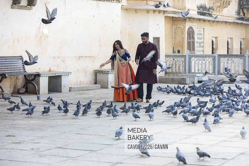 A young traditionally-dressed Indian couple feeds a flock of pigeons. <br><br><span style='color: red'>Editorial Use Only.</span><br><br>