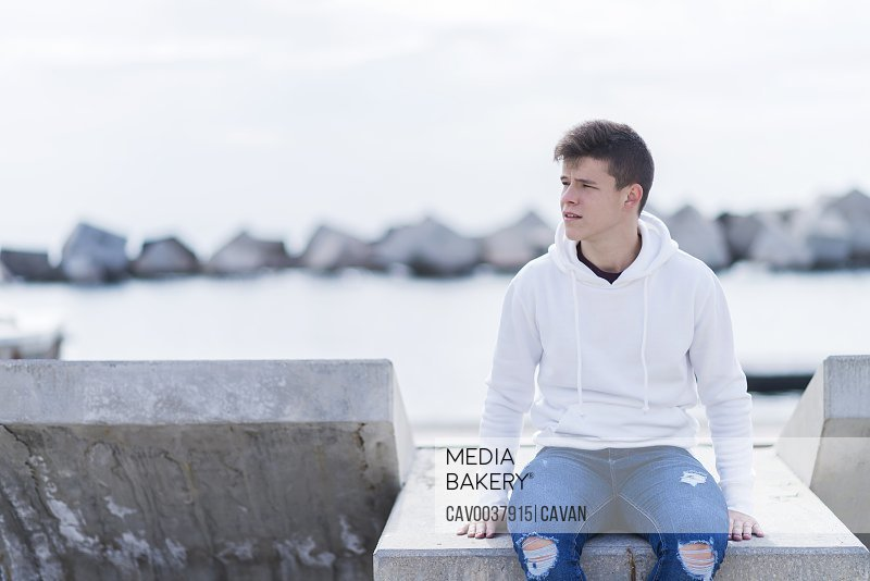 Front view of a teenager wearing casual attire while sitting on a bench outdoors and looking away