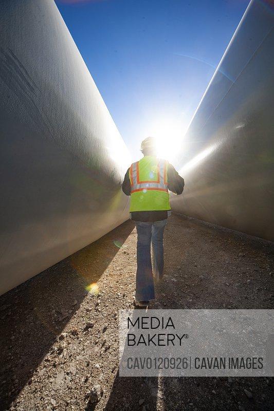 Person walks between blades at wind farm in Ft. Davis, Texas