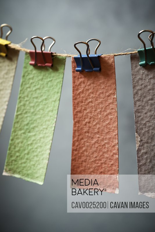 Watercolor test cards hanging on a rope.