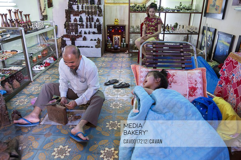A Vietnamese craftsman works while his daughter laughs at him. <br><br><span style='color: red'>Editorial Use Only.</span><br><br>