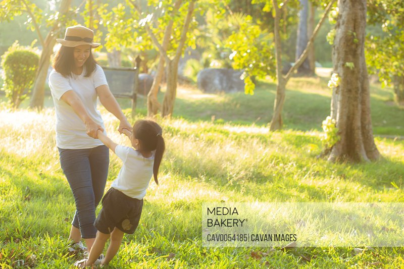 Young asian mother and little daughter playing the park with fun