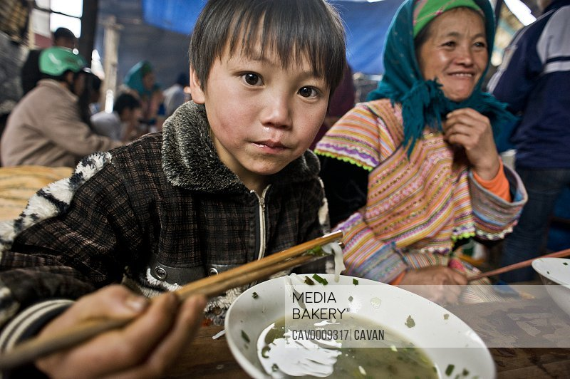 Young Hmong boy enjoying a bowl of soup in Bac Ha traditional market <br><br><span style='color: red'>Editorial Use Only.</span><br><br>