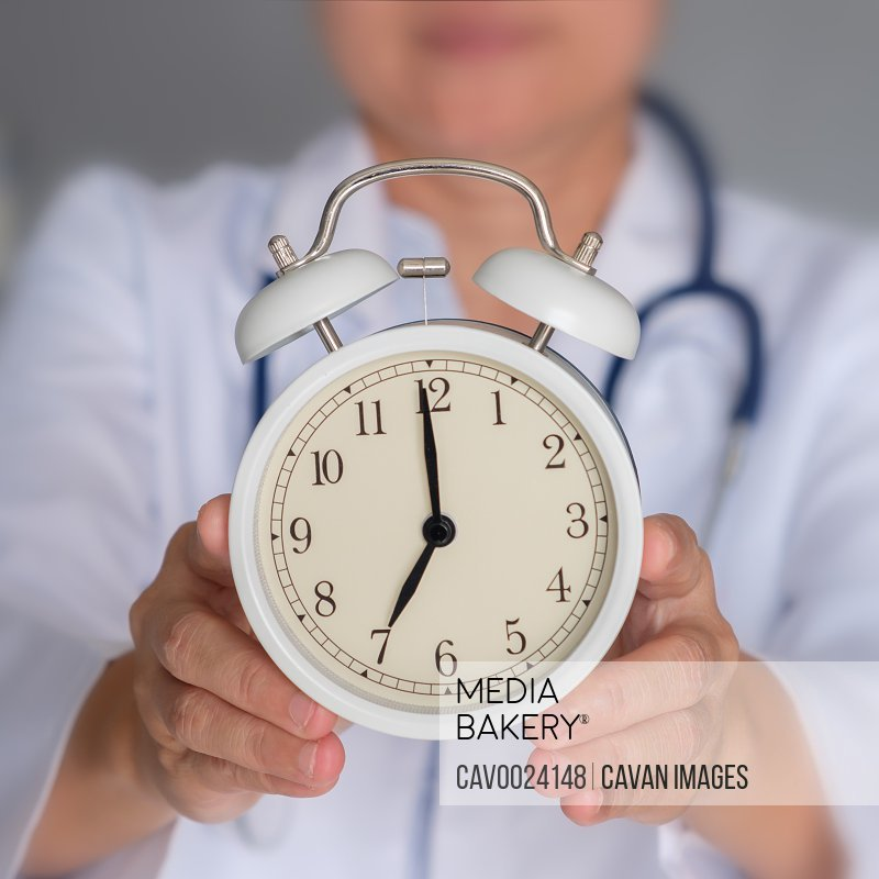 Doctor is holding alarm clock