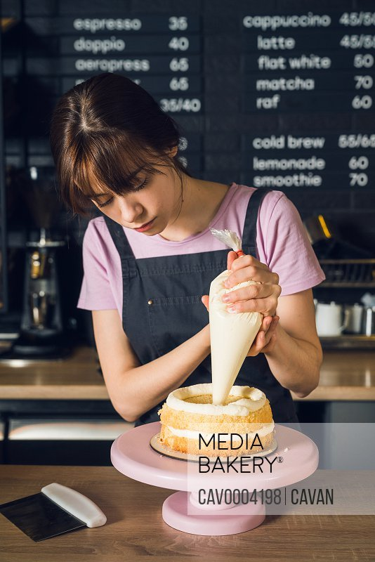 Woman in a dark apron decorate cake, squeezes out vanilla cream on cake in kitchen cafe