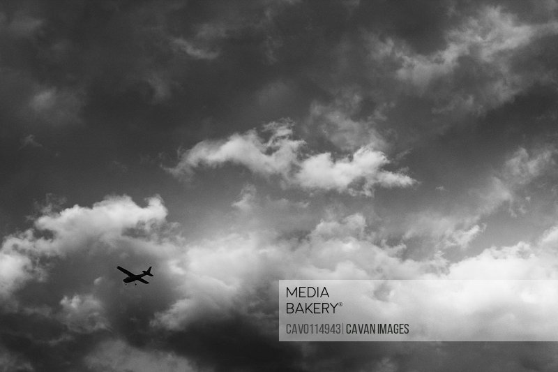 Black and white airplane flying above with cloud contrast