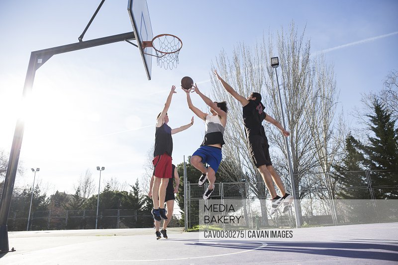 People playing basketball in summer
