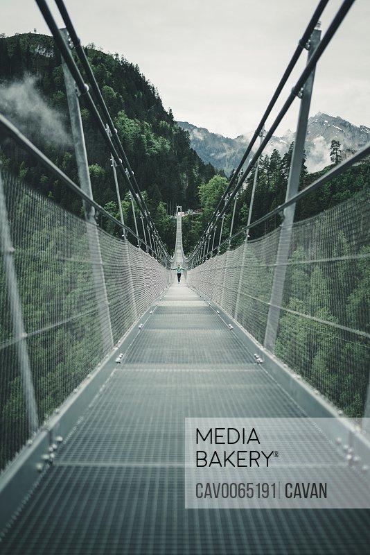 Young female crossing suspension rope bridge in alpine environment