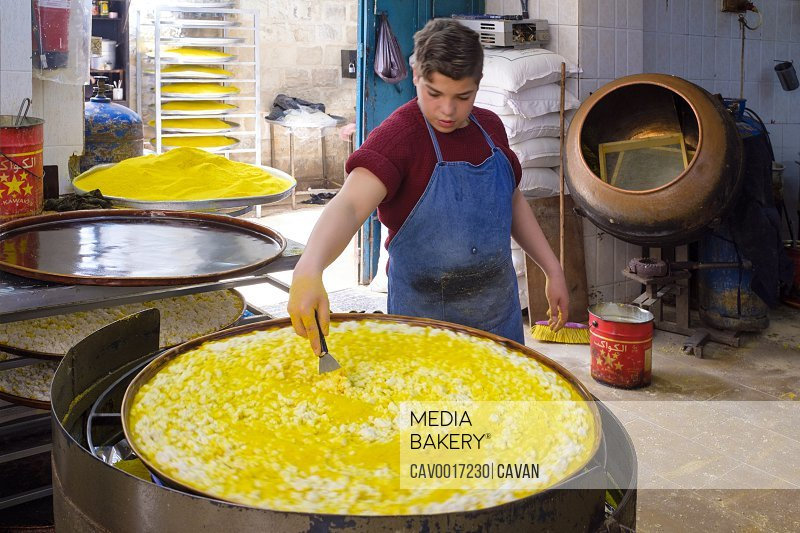 Boy preparing Knafeh at al-Aqsa Sweets, Nablus, West Bank, Palestine <br><br><span style='color: red'>Editorial Use Only.</span><br><br>