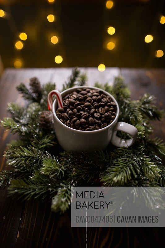 Close up of high angle coffee beans in coffee cup with holiday lights