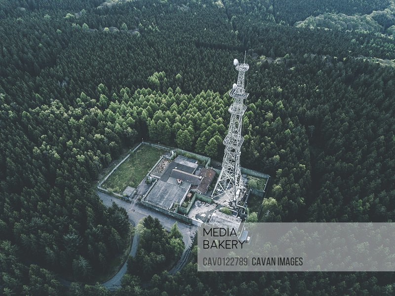 AERIAL: Drone Shot of old Abandones Radio Tower Station in Rich Green Forest surrounded by Trees