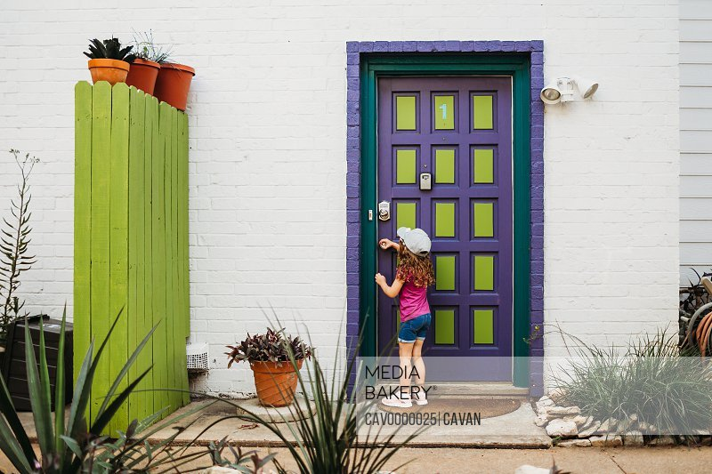 Young girl opening purple and green door by herself