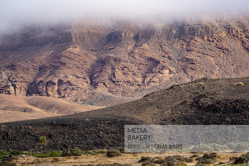 misty mountain of the Namibian desert. In the foreground a rocky hill
