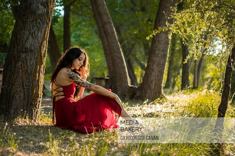 Young woman poses in a forest at sunset. Fantasy.