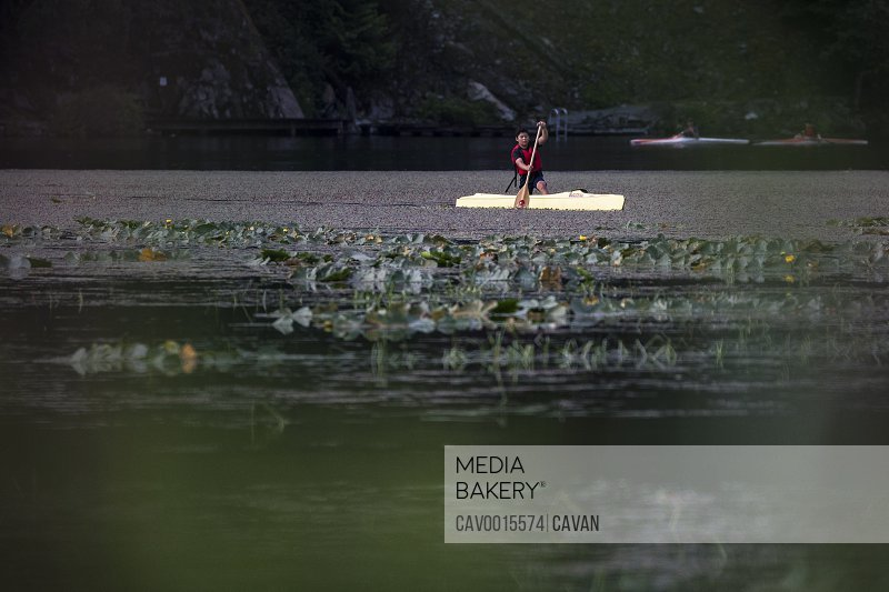 A boy canoes on a summer morning on One Mile Lake in British Columbia. <br><br><span style='color: red'>Editorial Use Only.</span><br><br>