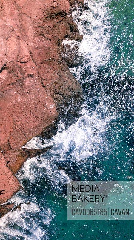 Aerial shot of waves splashing on rocky beach in California