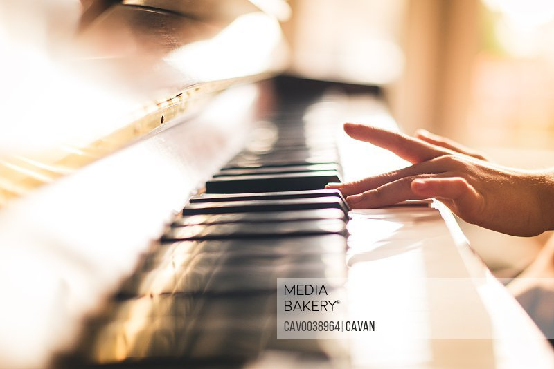 Close up image of child's hand playing piano in a sunny room.