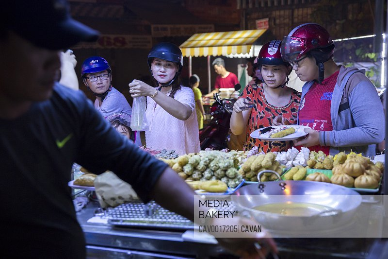 Customers buy food at a night market in the Mekong Delta, Vietnam. <br><br><span style='color: red'>Editorial Use Only.</span><br><br>
