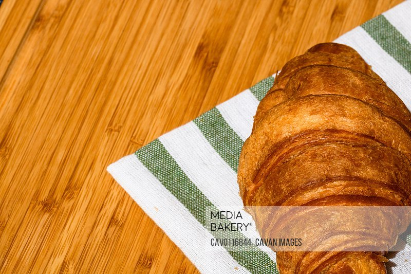 Detail of fresh croissant on wooden table. Food and breakfast concept. Close up photo of French buttery croissant