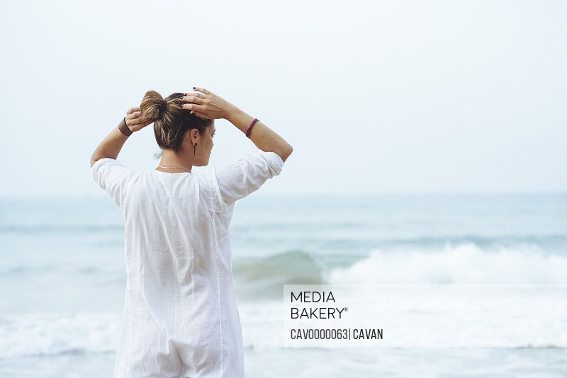 Pretty woman with white dress  arranging the hair on the beach.