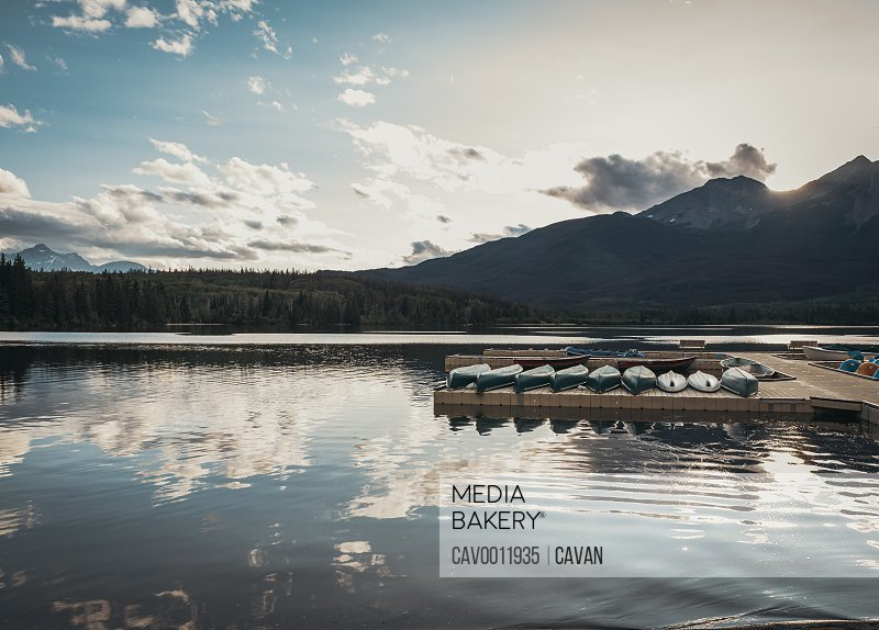 Line of canoes on a dock at sunset on Pyramid Lake in Jasper, Alberta.