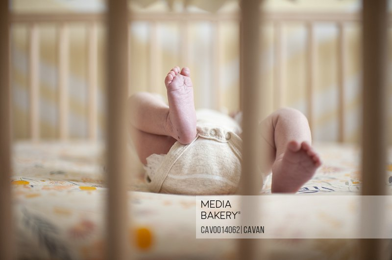 Newborn baby girls feet through crib at home